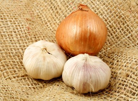 nutriments: Garlic and onion on a brown rustic fabric. Stock Photo