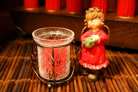 Angel figures-figurines with Christmas colors and a candle, decoration with warm light. photo