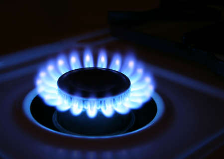 scintillation: Bluish flames of a stove burner in total darkness illustrating combustion.