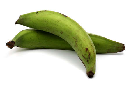 Green plantains on a white background, stacked among themselves. photo