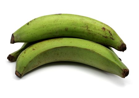 aliment: Green plantains on a white background, stacked among themselves. Stock Photo