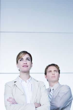 strong growth: front view of businessman and businesswoman standing looking