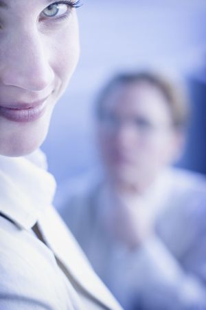 Beautiful businesswoman and man look off in same direction with womans face up close and mans face blurred in the background LANG_EVOIMAGES