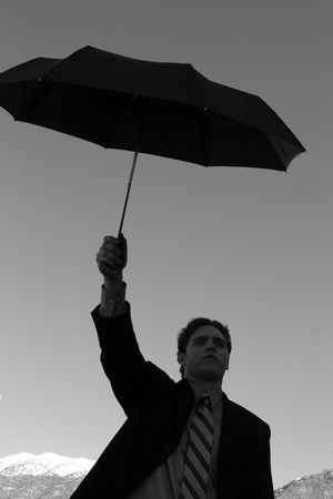 Businessman wearing suit and tie is holding an umbrella with mountains in the background Stock Photo - 3083821