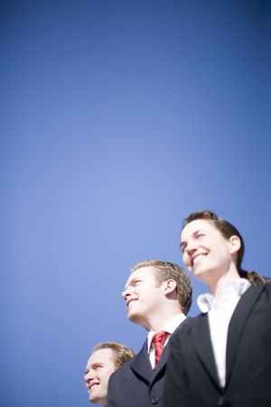 three happy business people looking in same direction wearing suits Stock Photo - 3083822