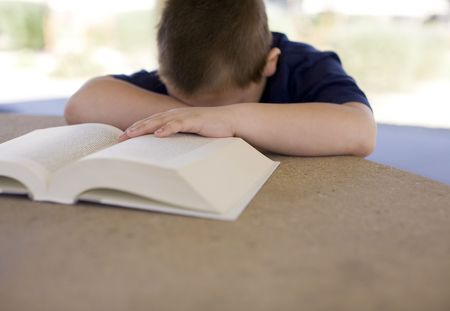 a child has his head down on the book being frustrated at reading because reading is difficult for children