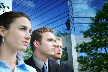 A group of three business people standing together outside against a blue business building in their business suits and business clothes