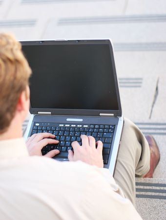 A business man is sitting on the steps outside using his laptop computer in a wireless connection
