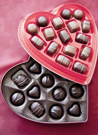 Two boxes of valentines day chocolates are together with the red box of chocolates on top of the dark box of chocolates on a red background Stock Photo