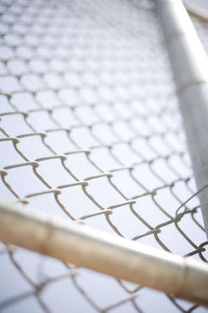 chainlinked: Close-up van een hek met twee grote balken in de voorkant van de keten gekoppelde hek