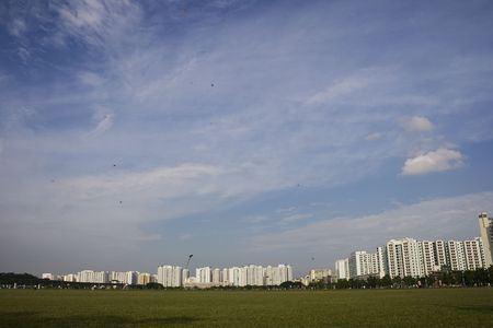 A Singapore landscape with a green grass field in front ground. Stock Photo