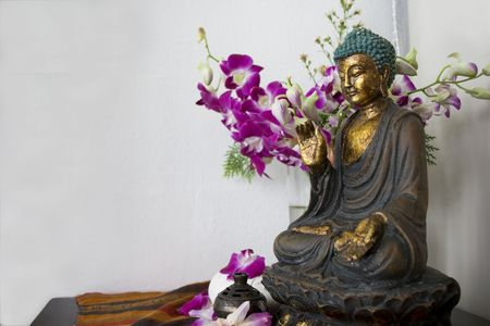 A traditional Chinese Buddha statue with flower at background. photo