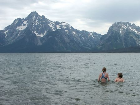 Swimming in Freezing Waters - two children facing the Grand Teton Range, Wyoming, in the background. photo