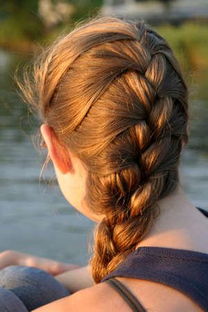 trenzas en el cabello: Joven mujer que relajaba a la puesta del sol