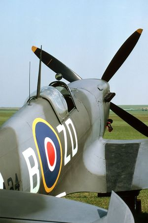 Cockpit of a mark IX British Spitfire parked beside a grass runway. Stock Photo