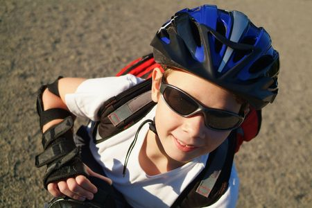crouches: A nine year old boy wearing sunglasses, a bike helmet and a backpack crouches in a sunny park.