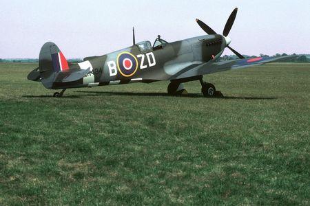 ix: British mark IX Spitfire parked beside a grass runway.