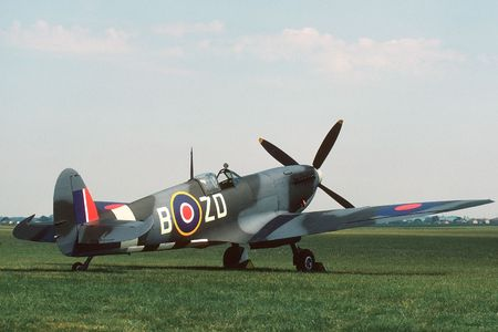 British mark IX Spitfire parked beside a grass runway.