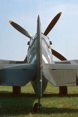 Tail of a mark IX British Spitfire parked beside a grass runway. Stock Photo - 561671