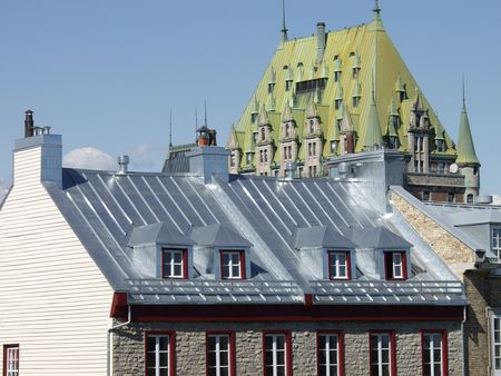 The roof of the Chateau Frontenac towers over a house in Old Quebec City, Quebec, Canada. Stock Photo
