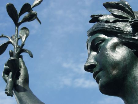 Statue of a goddess holding an olive branch against a clear blue sky, in Montreal, Quebec, Canada. photo