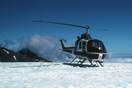 A helicopter perches on the edge of a glacier on the south island of New Zealand in 1983.