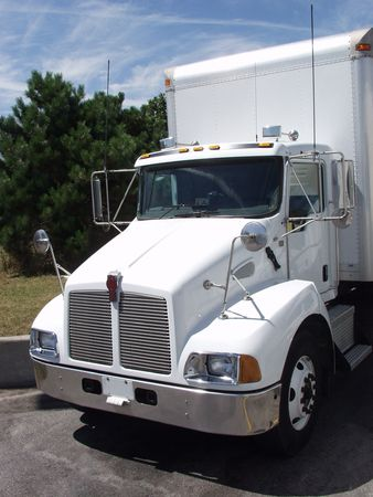 A white truck stands in the sunshine at a freeway rest area in North America.