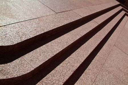 layers levels: A low sun casts dramatic shadows on three pink stone steps.
