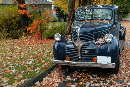 A vintage pickup truck stands under a maple tree in the fall.