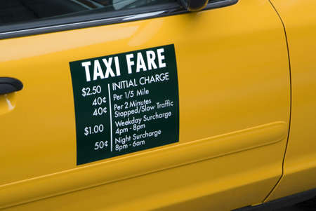 fare: Taxi fares displayed on the side of a yellow cab in New York City.