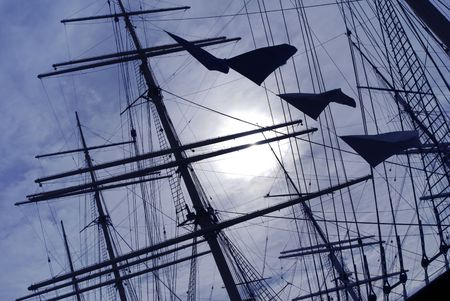 shrouds: Masts and rigging silhouetted against a dappled sky.