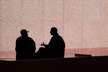 Two men having an animated conversation are silhouetted against a pink stone wall.