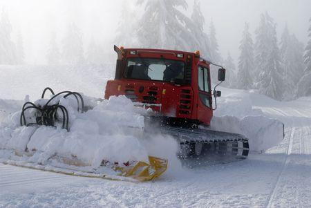 A snowplow prepares a run at a ski resort. photo