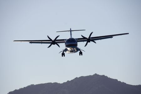 A twin-engined turboprop passenger plane landing at dusk. photo