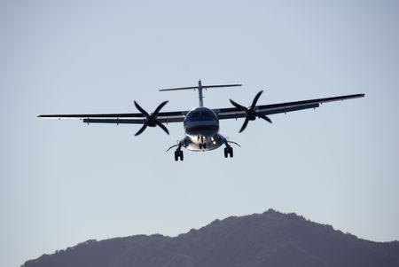 turboprop: A twin-engined turboprop passenger plane landing at dusk.