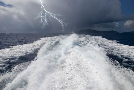 The wake from a high-speed boat as it heads away from a storm.