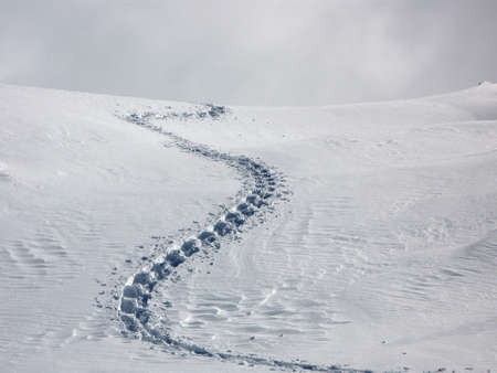 A single trail of footprints in deep snow. Stock Photo