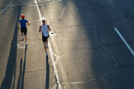 A pair of marathon runners head towards the rising sun during the opening stages of a race. Stock Photo - 832842