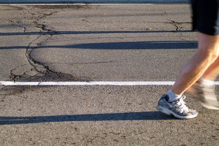 A marathon runner heads into the sun during the early stages of a race. Stock Photo - 832841