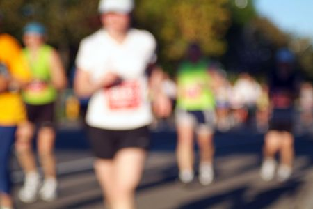 Marathon runners head into the sun during the opening stages of a race. Stock Photo