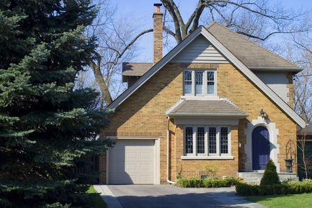 pitched roof: A North American yellow brick house in early summer. Stock Photo