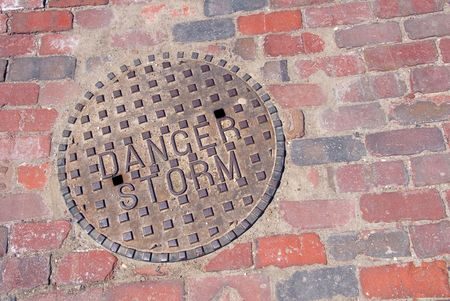 a round of inspection: A cast iron storm drain cover set into a red brick road. Stock Photo