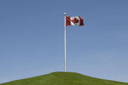 thee: A Canadian flag stands atop a grassy hill against a bright blue sky. Stock Photo