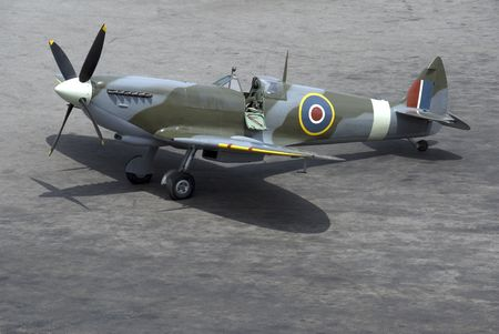 A British Spitfire fighter plane stands ready for action on an oil-stained airfield. Stock Photo - 1079495