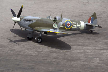 A British Spitfire fighter plane stands ready for action on an oil-stained airfield.
