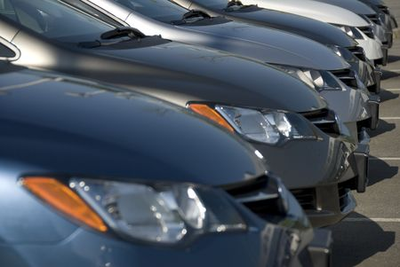 row: A lineup of new cars at a dealership. (Shot with minimum depth of field. Focus is on the third vehicle from the front.) Stock Photo