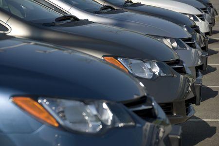 parked: Een lineup van nieuwe auto's bij een dealer. (Shot met minimale diepte van het veld. De focus ligt op de derde voertuig van de voorzijde.) Stockfoto