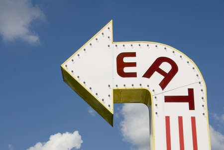 A three-dimensional metal EAT sign in a sans-serif typeface. photo