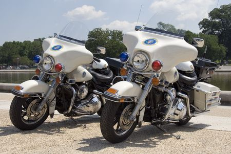 a white police motorcycle: Two Secret Service motorcycles stand near the Reflecting Pool on The Mall in Washington, DC.