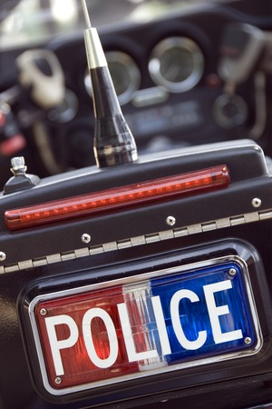 A red white and blue police sign on the back of a motorcycle. (Shot with minimum depth of field. Focus is on the sign.) Stock Photo - 1448510